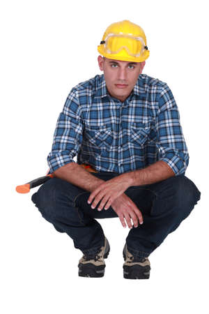 emotionless: Squatting tradesman with a piercing stare