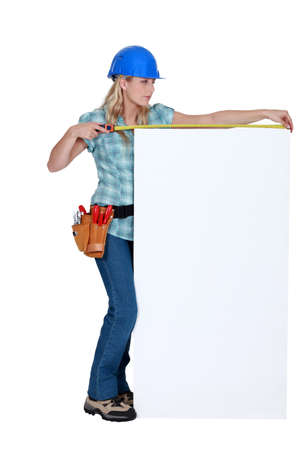 Construction worker measuring a blank board Stock Photo - 15411707