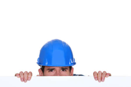 Builder peering over blank poster photo