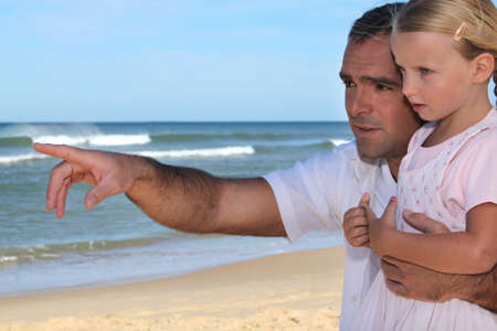 Father and daughter pointing at something on the beach photo