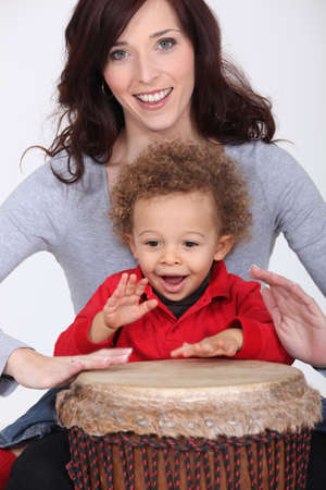 music therapy: Little boy and mother playing bongo drum