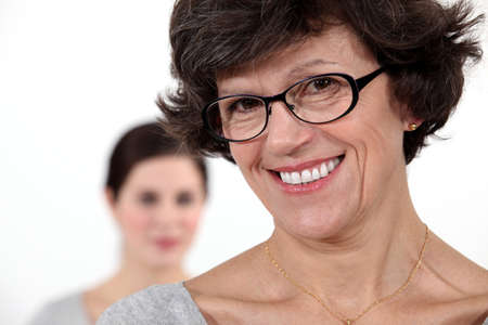 progeny: Mother stood with daughter in background Stock Photo