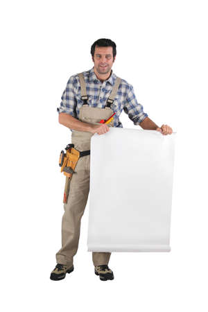 Handyman unrolling a plan Stock Photo - 15448439