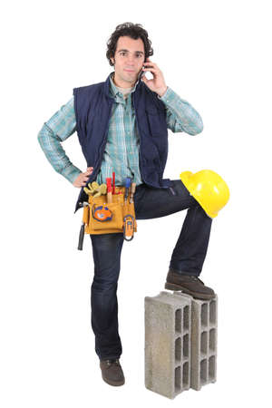 stonemasonry: Portrait of a tradesman talking on his mobile phone and his foot propped up on a block