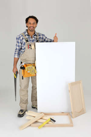 Woodworker stood with cabinet door and advertising panel photo