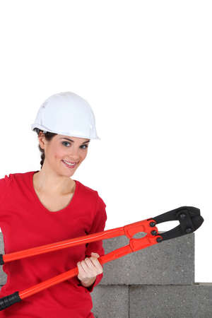 female construction worker: young female bricklayer posing with pliers against concrete wall background Stock Photo