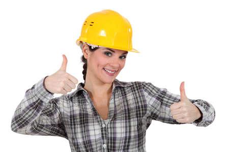 assentiment: Tradeswoman sourire donnant deux pouce de neuf