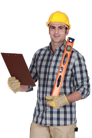 adjusted: Worker holding spirit level and clip-board Stock Photo