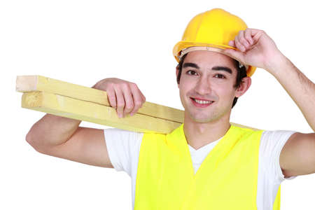 apprentice: young carpenter with hand to hard hat carrying planks
