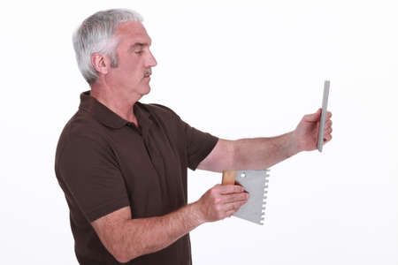 accurately: Man fitting tiles Stock Photo