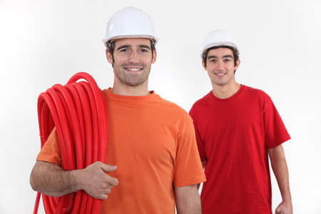 Plumber and assistant stood with coil photo