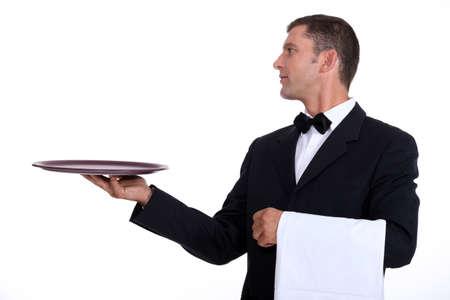 camarero: Un camarero que sostiene una bandeja vacía