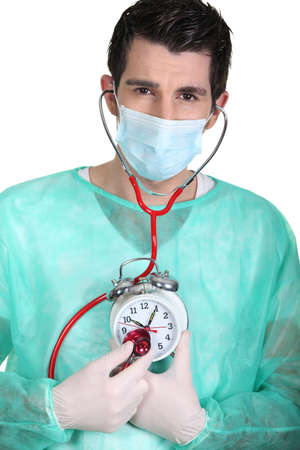 Doctor listening to an alarm clock's heartbeat Stock Photo - 15448522