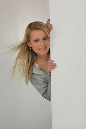 Woman sticking out behind the wall Stock Photo - 15448476