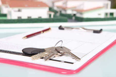 refinance: House keys resting on clip-board Stock Photo