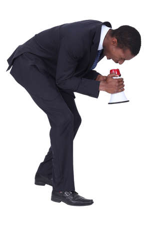 bent over: Man in suit shouting into megaphone Stock Photo