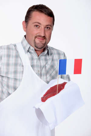 Butcher holding a piece of steak spiked with the French flag photo