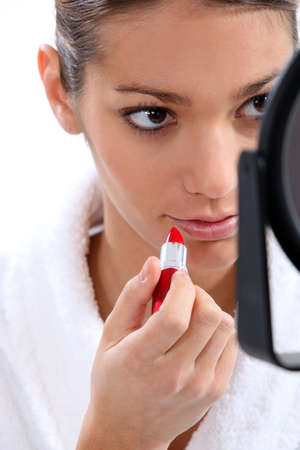 Woman putting on lipstick photo