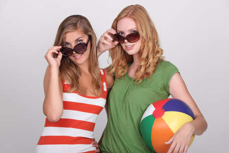 sorority: Two young woman with summer shades and a beach ball Stock Photo