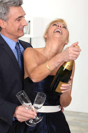 popping cork: Couple celebrating their anniversary