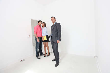 Estate agent showing couple around property photo
