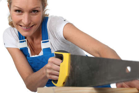 Woman sawing wood photo