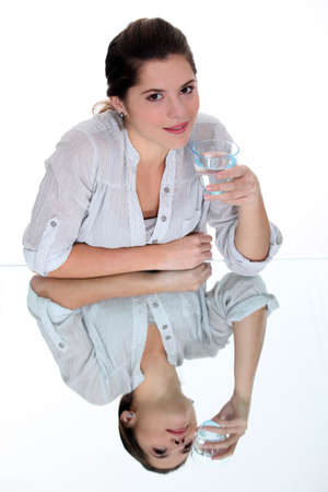 Young woman drinking a glass of water on a mirrored table photo
