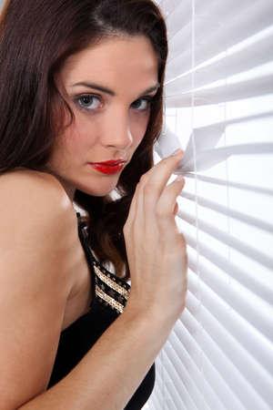 peering: Woman peering through blinds