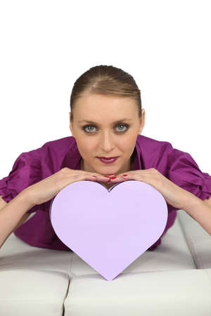 Young woman lying with heart-shaped box photo