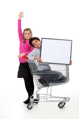 niño empujando: Niños en un carro de la compra con una tarjeta en blanco Foto de archivo
