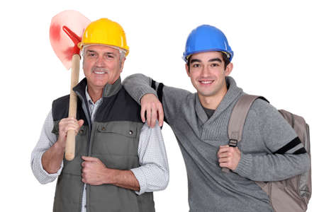 Experienced tradesman posing with his new apprentice photo