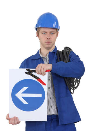 superintendence: Electrician with a one way sign Stock Photo