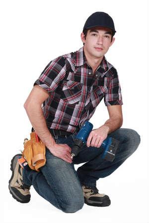arrodillarse: Comerciante joven que sostiene un destornillador recargable