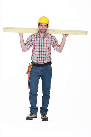 Tradesman carrying planks of wood photo