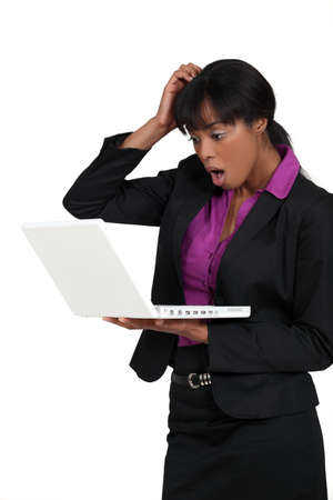 dismayed: Businesswoman staring in shock at her laptop Stock Photo