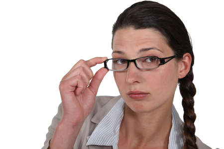 poker faced: Woman adjusting her glasses Stock Photo