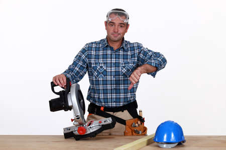 Thumbs down from a man with a circular saw Stock Photo - 15449650