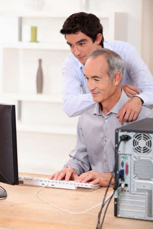 A father and a son looking at a computer screen  photo