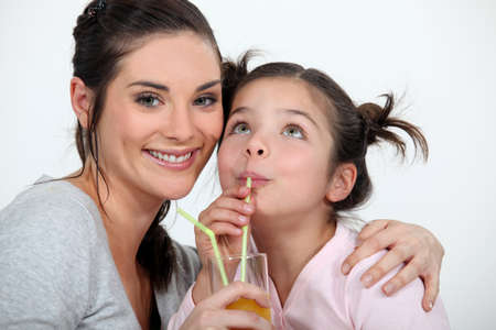 Mother and daughter drinking through straws photo