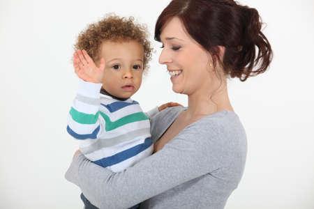 curare teneramente: Bambino in giovane et� salutava con la mano