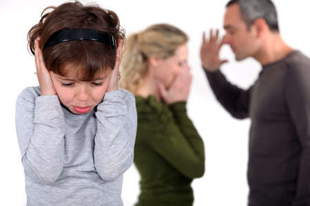 Young girl trying to block out the sound of her parents arguing photo