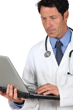 45 49 years: Doctor in a white coat and stethoscope with a laptop computer Stock Photo