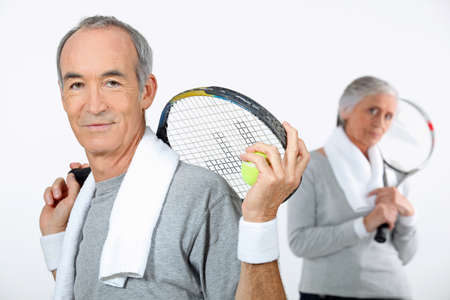 Older couple with tennis rackets photo