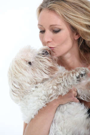 Middle-aged woman kissing dog. photo