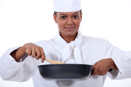 chinese hat: Woman chef stirring a wok Stock Photo