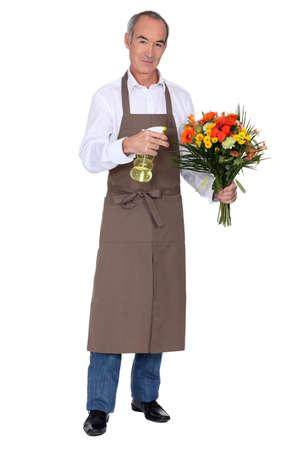 arranging: Florist spraying a bouquet of flowers
