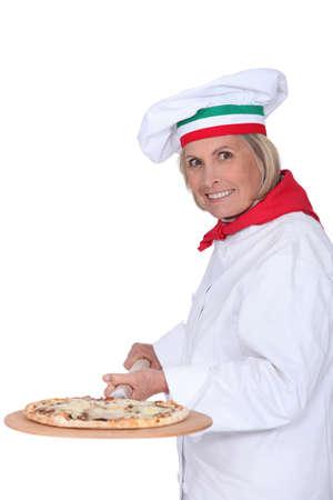 Senior female cook preparing pizza photo