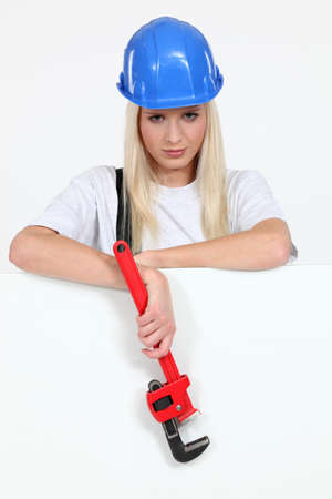 hammer head: Woman stood by blank poster holding wrench Stock Photo
