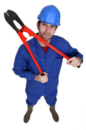 casco rojo: Trabajador de la construcción que sostiene los alicates grandes