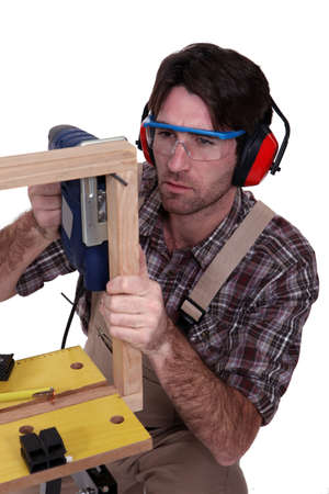 eye protection: A male carpenter using a jigsaw. Stock Photo